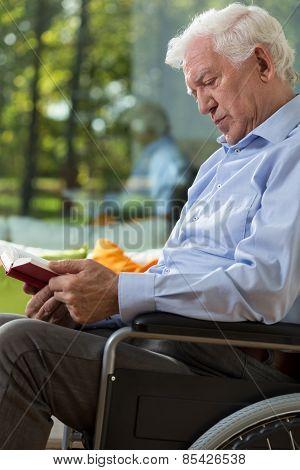 Man On Wheelchair Reading Book