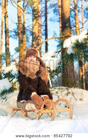Beautiful Cheerful Girl Sitting On Sledges Contemplating Winter Forest.