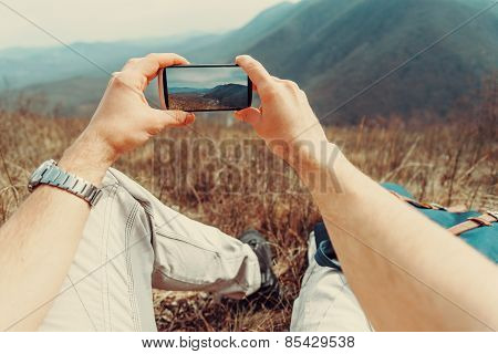 Man Taking Photographs Mountain With Smartphone