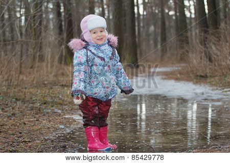 Two Years Old Girl Standing In Icy Puddle