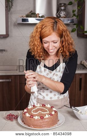 Happy Woman Decorating Cake At Home