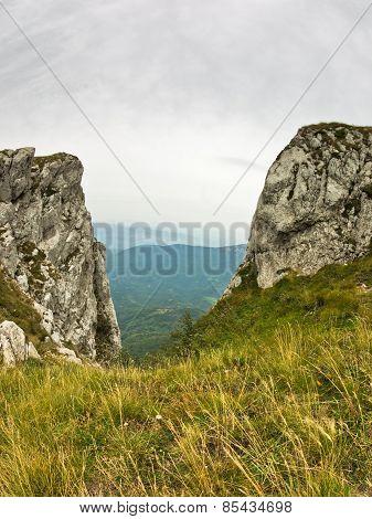 Rocks and cliffs under dark clouds trekking path at Suva Planina mountain