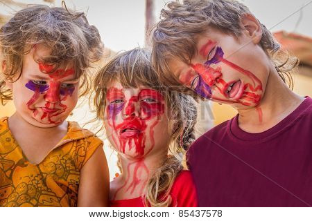 three young kids - boy and girl - with painted faces, child zombie face art