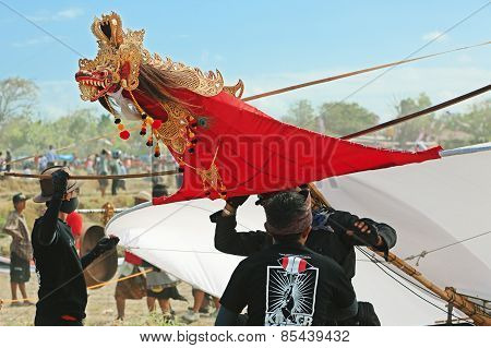 Young men preparing to launch a huge kite with a dragon head