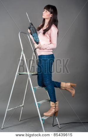 Attractive woman on ladder with heavy drill