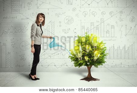 Business woman pouring water on lightbulb growing tree concept