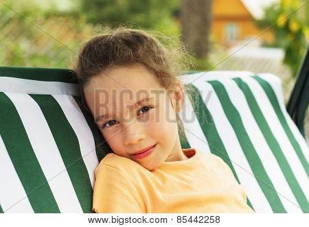 Beautiful sad school girl is resting against green of summer park.