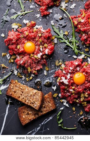 Beef Tartare With Fresh Toasts On Dark Marble Background