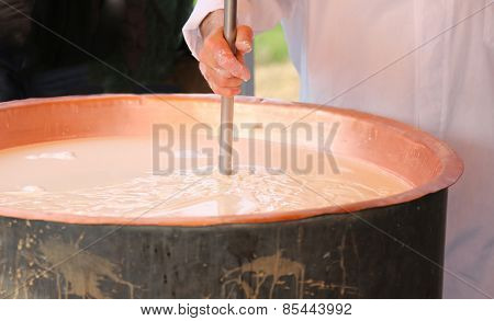 Hands Of Elder Cheesemaker Mixes The Milk In Copper Pot For Cheese