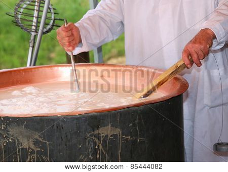 Cheesemaker Checks The Temperature Of The Boiling Milk In The Pot