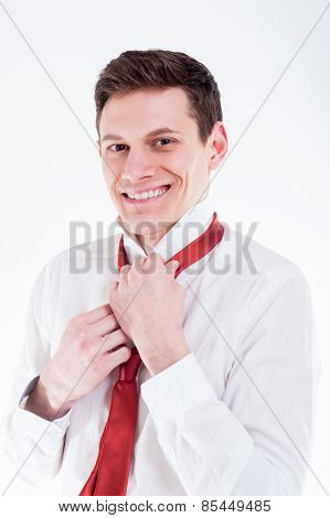 Young businessman tying a red tie