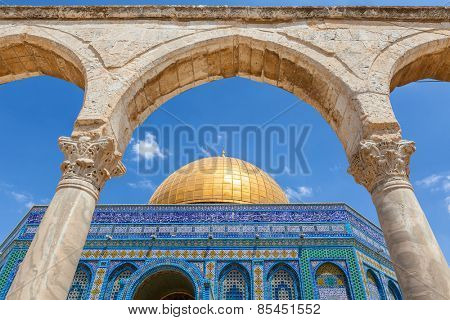 Ancient arch and Dome of the Rock Mosque under blue sky in Jerusalem, Israel.