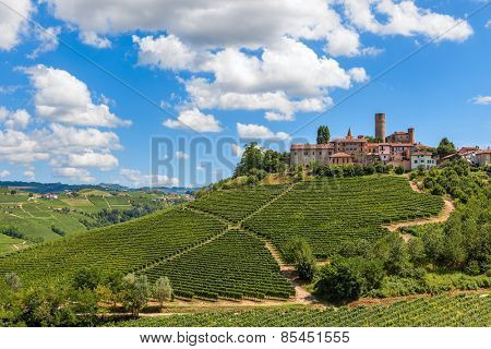 Small town on the hill with green vineyards under blue sky with white clouds in Piedmont, Northern Italy.