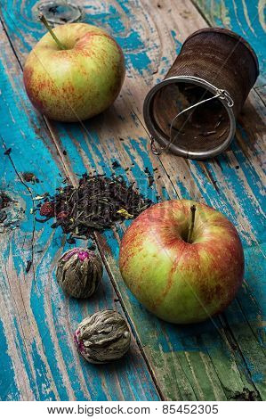 Tea Leaves And Red Apple On Wooden Background