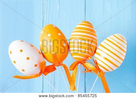 Orange patterned easter eggs on blue wood background