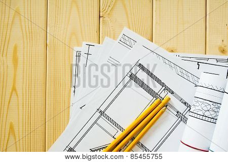Many drawings for building and pencils on a wooden background.