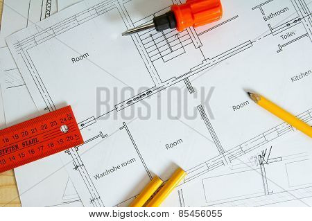 Repair work. Drawings for building and screwdriver on wooden background.