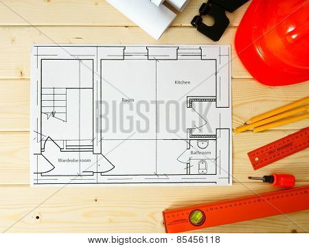 Repair work. Drawings for building, screwdriver, helmet and others tools on wooden background.