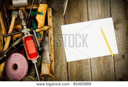 Paper with a pencil and old tools in box on wooden background.