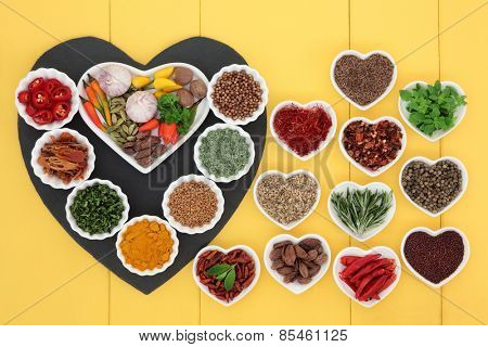 Herb and spice ingredients on a heart shaped slate and porcelain dishes over wooden yellow background.