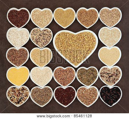 Grain and cereal food selection in heart shaped porcelain bowls over lokta paper background. Kamut khorasan wheat in large dish.