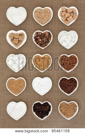 Brown and white sugar selection in heart shaped bowls over hessian background.