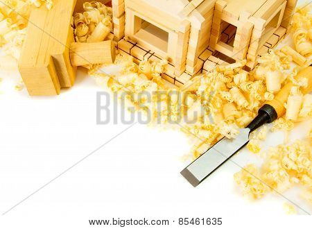 House construction. The small wooden house, chisel, plane and shaving on white backg
