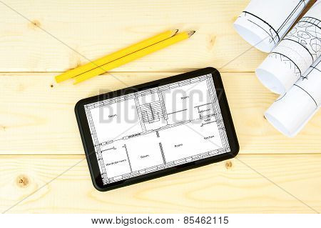 Tablet, drawings and pencils on a wooden background.