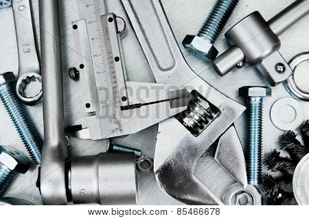 Metal tools on the scratched metal background.