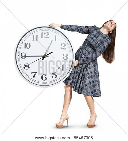 young woman holding heavy white clock. isolated on white background