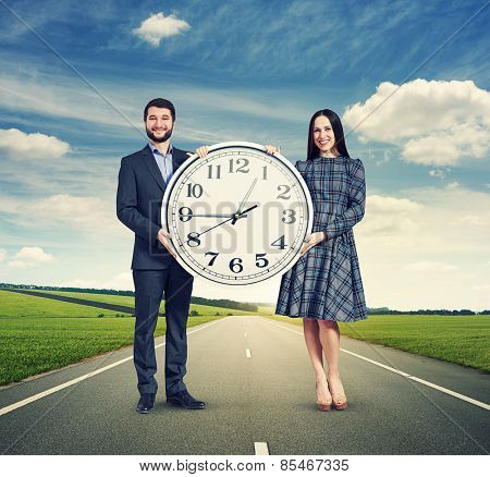smiley couple holding white clock and looking at camera. photo at outdoor