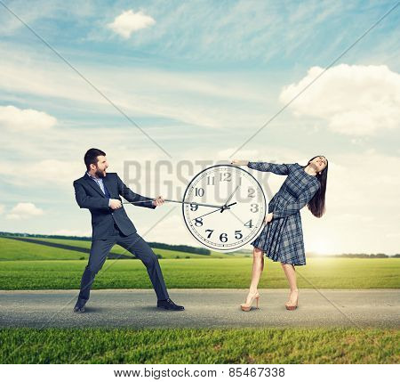 emotional couple with clock at outdoor