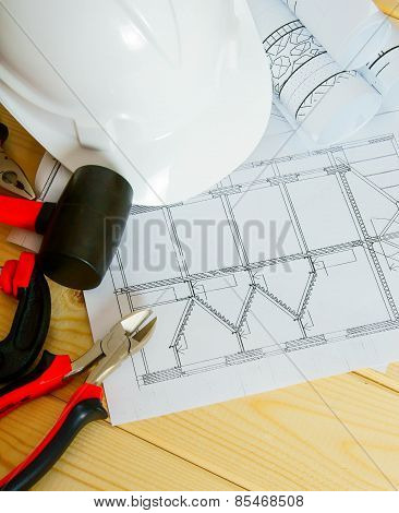 House construction. Drawings for building, helmet and others tools on wooden background.