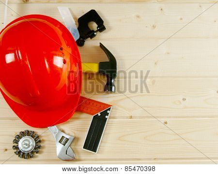 helmet, hammer, an adjustable spanner and other tool on a wooden background.