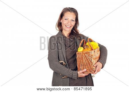 Beautiful woman coming from the market with a basket full of fruits and flowers