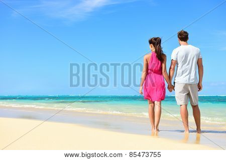Summer holidays - couple on tropical beach vacation standing in white sand relaxing looking at ocean view. Romantic young adults holding hands in beachwear with pink dress and surf shorts in love.
