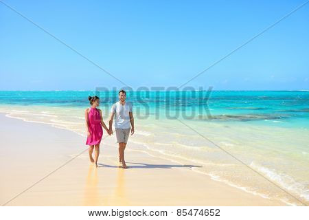Summer vacation couple walking on beach landscape. Young adults relaxing together enjoying their holidays in perfect getaway in sunny tropical destination with pristine turquoise ocean water.