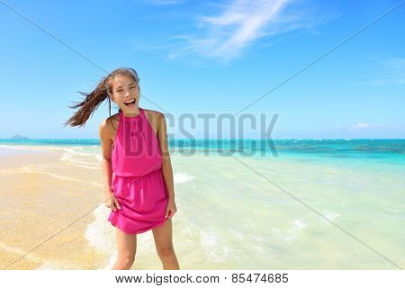 Asian Chinese tourist woman having fun on beach. Young mixed race female adult playing in water wearing pink halter sundress laughing during summer travel holidays. Tropical sunny destination.