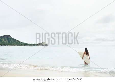 Surfer girl going surfing on Waikiki Beach, Oahu, Hawaii. Female bikini woman heading for waves with surfboard having fun living healthy active lifestyle on Hawaiian beach. Water sports with model.
