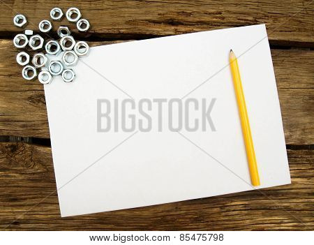 The Sheet of paper with a pencil and fixing elements, wrenches on wooden background.