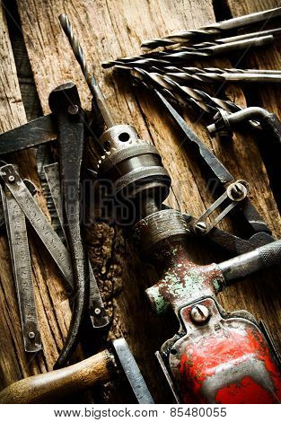 Old drill, compasses, pliers and drills on a wooden background.