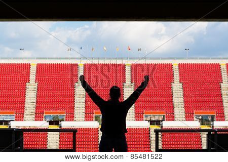 silhouette of female football fan from behind in a empty stadium