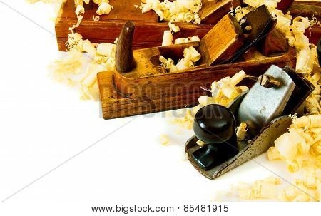 Joiner's works. Wooden shaving and plane on white background