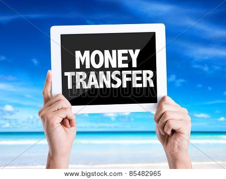 Tablet pc with text Money Transfer with beach background
