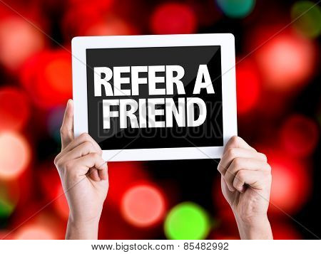 Tablet pc with text Refer a Friend with bokeh background