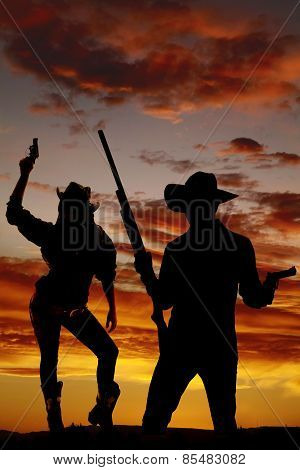 Silhouette Of Cowgirl Holding Up Gun In The Air
