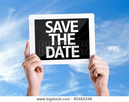 Tablet pc with text Save the Date with sky background
