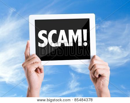 Tablet pc with text Scam! with sky background