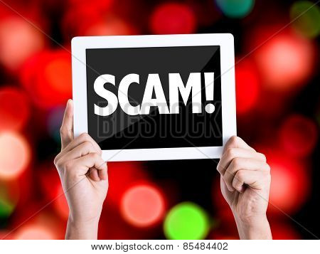 Tablet pc with text Scam! with bokeh background