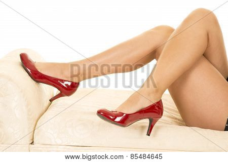 Woman Legs With Red Heels Crossed On Couch